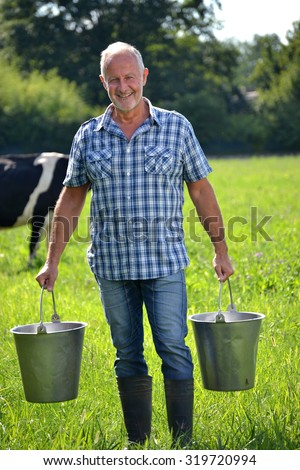 Farmer holding buckets after milking cow - stock photo
