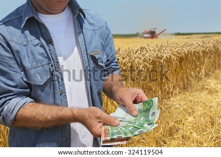 Farmer holding Euro banknote with combine harvester and wheat field in background - stock photo