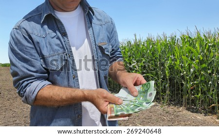 Farmer holding Euro banknote with green cultivated corn field in background