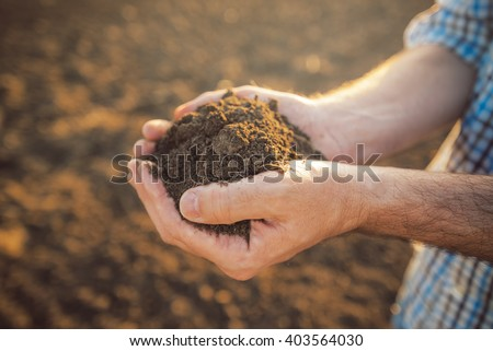 Farmer holding pile of arable soil in hands, responsible and sustainable agricultural production, close up with selective focus - stock photo