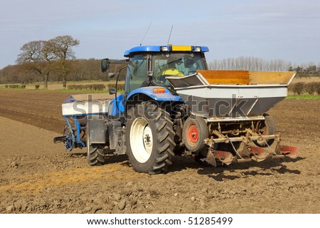 farmer in a blue tractor planting potatoes on a beautiful spring day in the english countryside