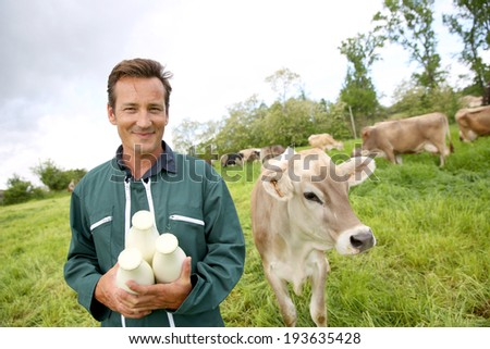 Farmer in field holding bottles of milk - stock photo