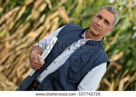 Farmer in field with laptop - stock photo