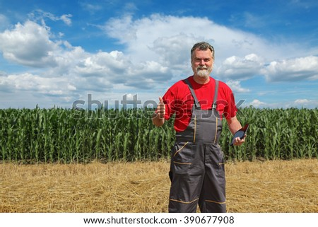 Farmer in front of green corn field smiling and gesturing with tablet in hand