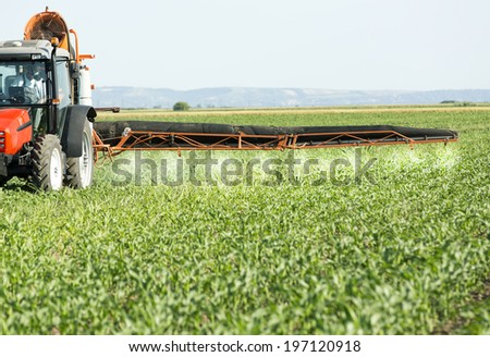 Farmer in red tractor spraying soybean field with herbicides, pesticides and fungicides - stock photo