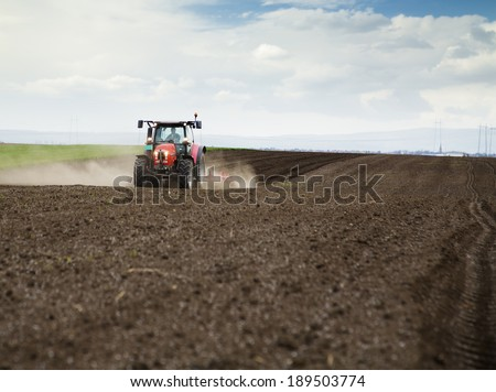 Farmer in tractor preparing land for sowing - stock photo