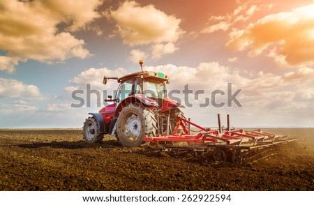 Farmer in tractor preparing land with seedbed cultivator - stock photo
