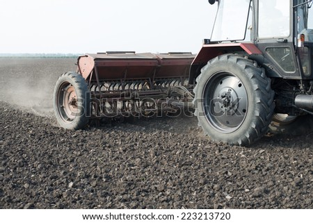 Farmer in tractor sowing crops at field with seed scattering agricult - stock photo