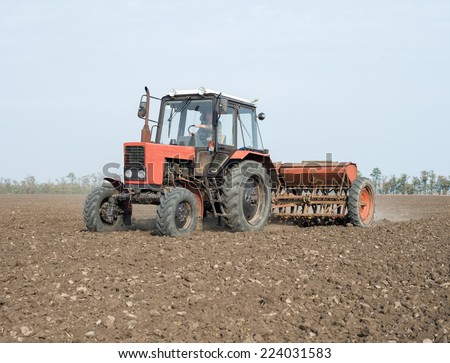 Farmer in tractor sowing crops at field with seed scattering agricult