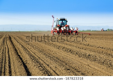 Farmer in tractor sowing crops at field with seed scattering agricultural machine - stock photo