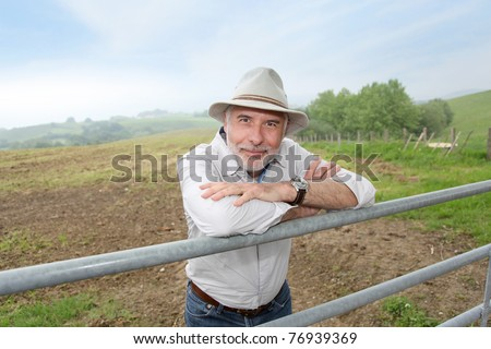 Farmer leaning on farmland fence