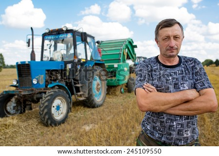 Farmer male in field standing on his tractor vehicle with hay bale maker farm machine background - stock photo