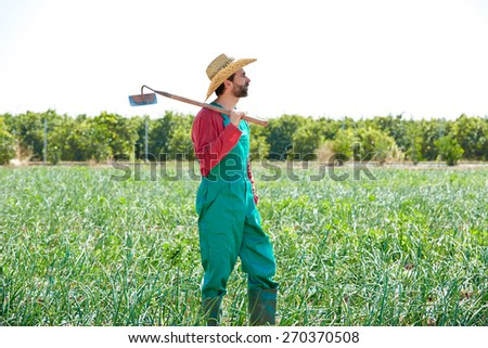 Farmer man with hoe looking at his orchard field with hat - stock photo