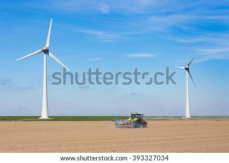 Farmer on tractor sowing in soil near dike and two windmills in the netherlands