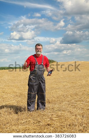 Farmer or agronomist in wheat field after harvest gesturing with tablet in hand