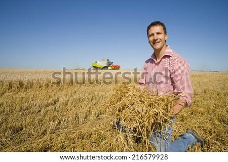 Farmer picking up straw - stock photo
