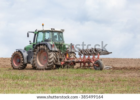 Farmer ploughing,  an overwintered fallow field for planting the spring crop  with a plough and tractor in a close up skyline view, focus to the implement