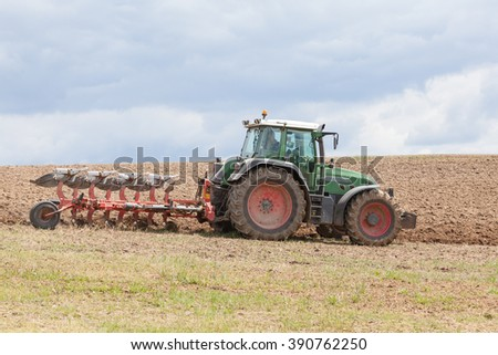 Farmer ploughing an overwintered fallow field with a tractor and  plow as he prepares the soil for  planting  the spring crop, close up side view