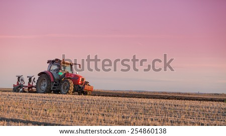 Farmer plowing field at sunset - stock photo