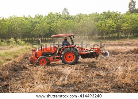 Farmer plowing stubble field with orange tractor