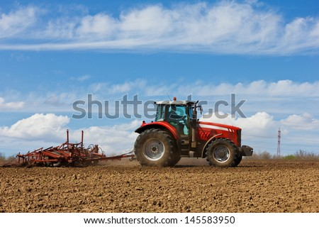Farmer plowing the field. Cultivating tractor in the field. Red farm tractor with a plow in a farm field. Tractor and Plow