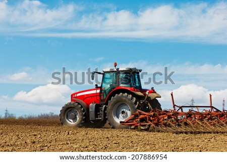 Farmer plowing the field. Cultivating tractor in the field. Red farm tractor with a plow in a farm field. Tractor and Plow - stock photo