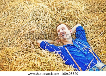 farmer relaxing on a hay  - stock photo