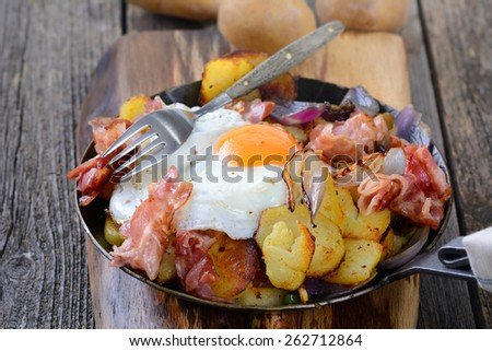 Farmer's breakfast with fried potatoes, fried egg and bacon served in an iron pan - stock photo