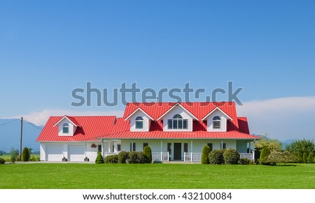 Farmer's family house with double garage green lawn in front and blue sky background. British Columbia, Canada