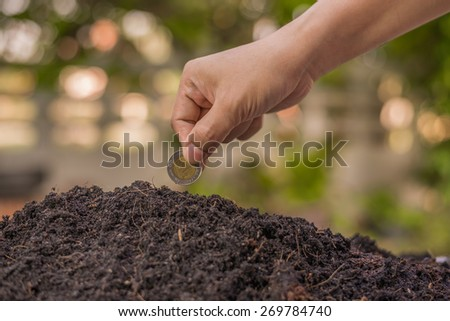 Farmer's hand planting coin in soil - stock photo