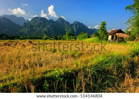 Farmer's hut on a field in Vang Vieng, Laos. Vang Vieng is a popular destination for adventure tourism in a limestone karst landscape.