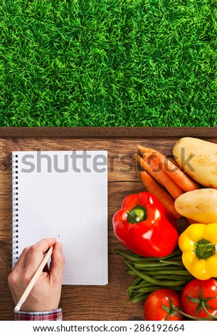 Farmer's notebook with fresh vegetables and green grass, male hand writing with a pencil
