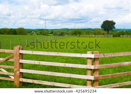 Farmer's wooden fence surrounding grassy field