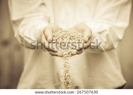 Farmer Showing Animal Dry Food in its hands - stock photo