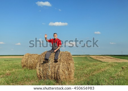 Farmer sitting at bale of hay in field and gesturing, waving