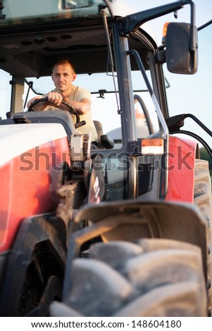 Farmer sitting in his tractor at sunrise - stock photo