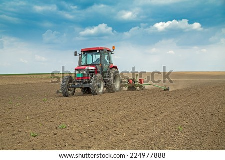 Farmer sowing corn maize crops - stock photo