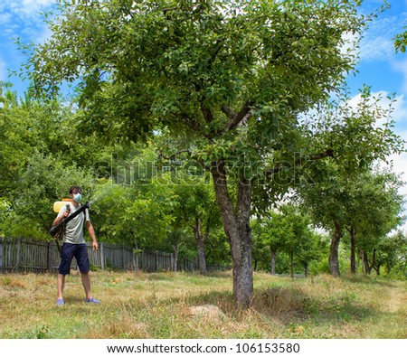 farmer spraying the trees with chemicals - stock photo