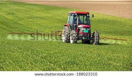 Farmer spraying wheat field at spring season, herbicides, pesticides - stock photo