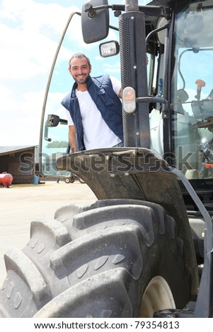Farmer standing by the cab of his large tractor - stock photo
