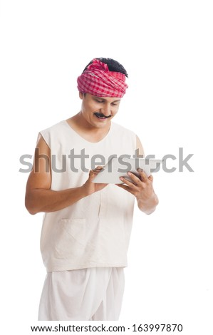 Farmer using a digital tablet and smiling - stock photo