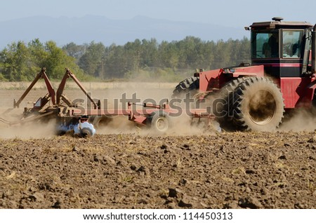 Farmer using a disc cultivator to break of soil after plowing on a field in Oregon