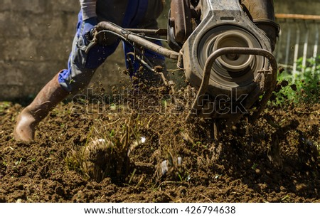 Farmer using machine mart cultivator for ploughing soil  - stock photo