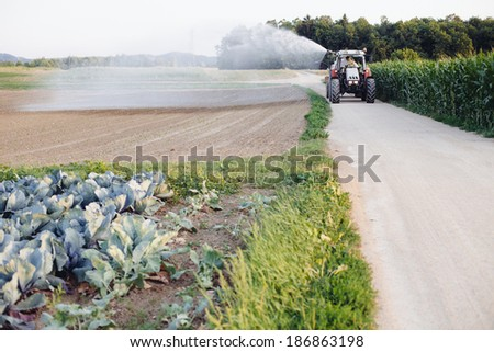 Farmer watering the field using tractor and cistern - stock photo