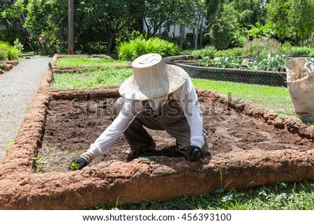 farmer wearing hat and white shirt is preparing soil for agriculture or farmland