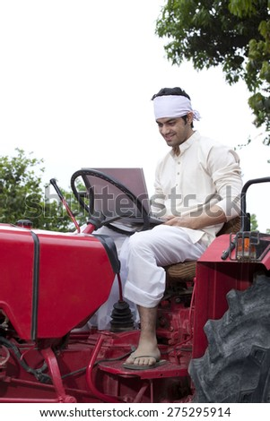Farmer with a laptop sitting on a tractor - stock photo