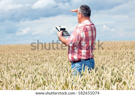 Farmer with computing machine in the field - stock photo