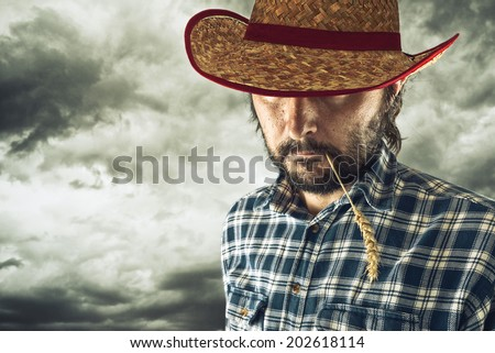 Farmer with cowboy hat and wheat straw in his mouth - stock photo