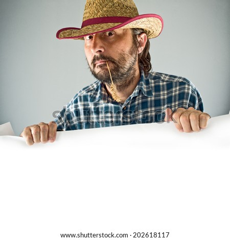 Farmer with cowboy straw hat holding blank poster as copy space