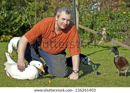 Farmer with his pet geese and ducks